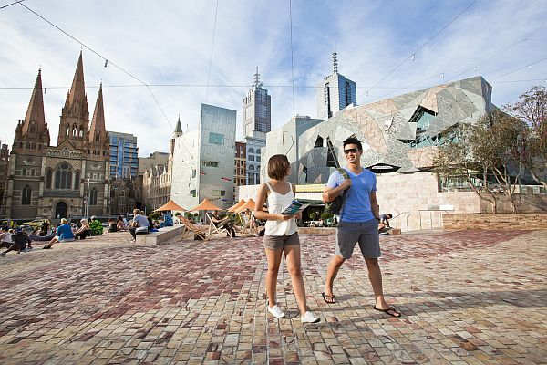 Couple walking through Federation Square